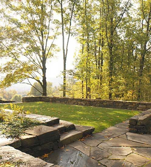 low stone wall enclosing lawn & patio area .  shepard butler landscape architecture