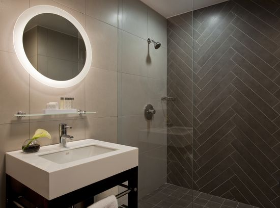 Check out this Modern Bathroom Design. Love the Herringbone tile accent wall and that round mirror! #TileSensations