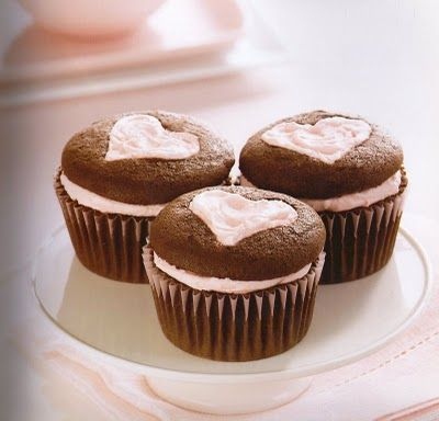 slice off top of cupcake and put frosting the bottom. use a cookie cutter to make cut out shape on the part of cupcake. replace top of cupcake on the frosting