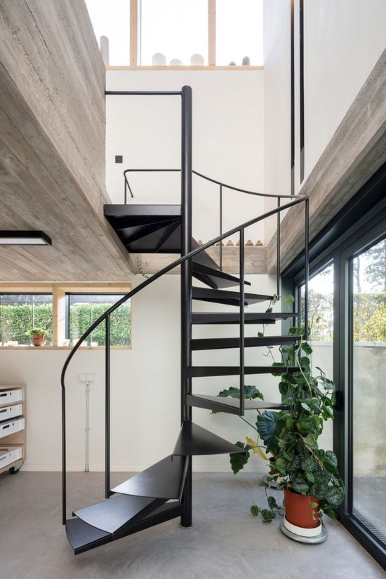 This workshop features a spiralling black steel staircase that leads to the upper level.
