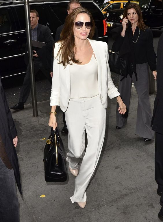 Angelina Jolie's Surprising Signature Style: Pantsuits!: When we think of Angelina Jolie's style, it's hard not to think of her extravagantly sexy gowns at the Oscars and the Cannes International Film Festival — or her simply classic wardrobe for days out with her children.: