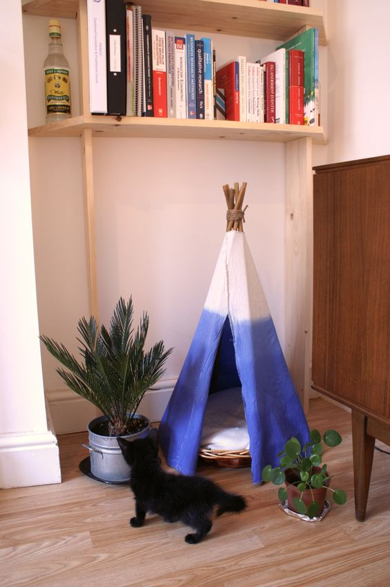 DIY cat teepee. Whicker basket with a bag of sand in the base so it doesn't flip over. Bamboo tied together with string and elastic.