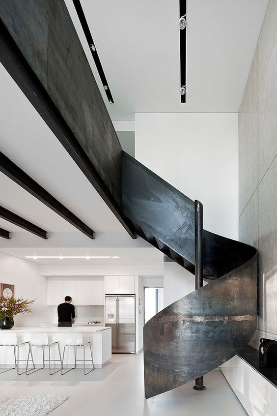 Modern apartment with a sleek sculptural staircase.