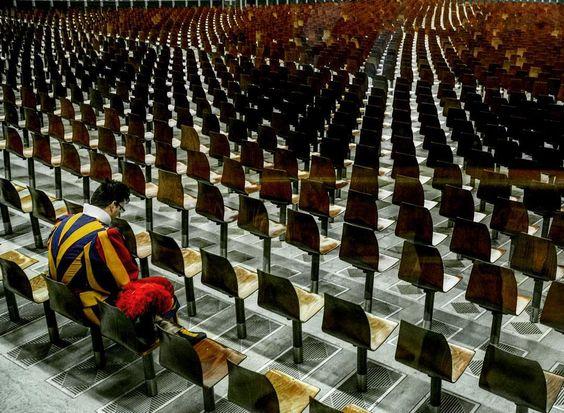 Un momento di pausa. Una guardia svizzera guarda il pavimento tra le sedie vuote. Un momento di pausa del sinodo straordinario sulla famiglia in Vaticano.  Foto: Pierpaolo Scavuzzo/Agf  #vaticano #roma #guardiesvizzere by lacronacaitaliana