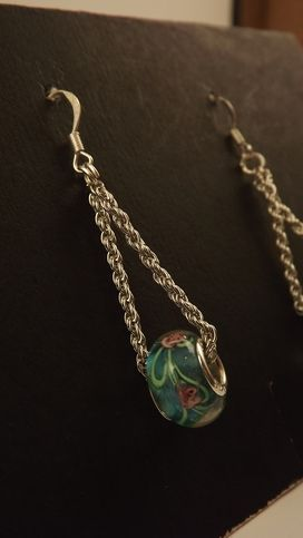 These are not Pandora, but they are just like they made so beautiful! These have a teal color to them and feature a pretty pink rose, that was worked into the bead, made with sterling silver cores, these cute earrings dangle 2 1/2 inches from the post on silver plated chains from silver plated fr...