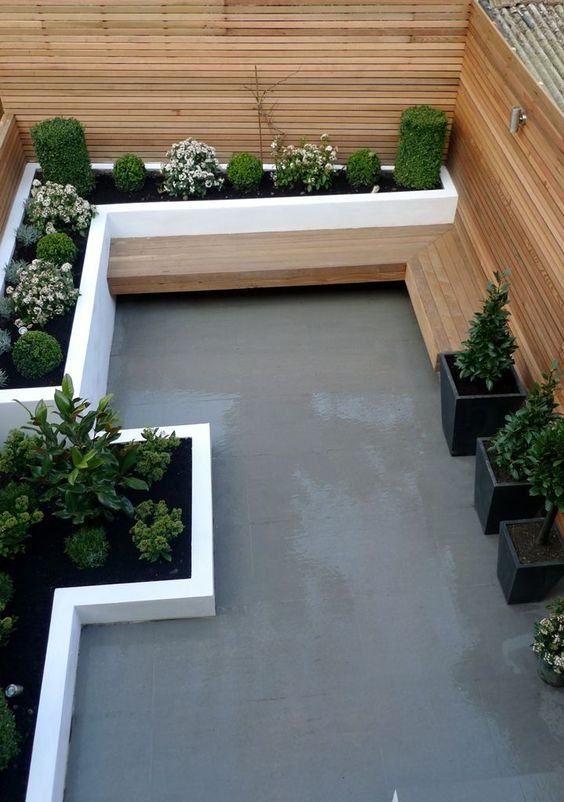 Stunning Modern London Small Garden Design. Grey tile paving, white washed rendered walls, floating hardwood seating bench with cedar privacy screen and chrome up lights. Create another room with luxurious materials designed to create a relaxing outdoor space that is low maintenance and a pleasure to use. Contactanewgardenfor more inform