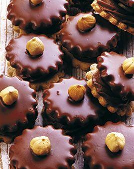 Mozarttaler - Rezept für Weihnachten - Für ca. 40 Stück: 100 g Butter, 60 g Puderzucker, 1 Prise Salz, Mark von 1 Vanilleschote, 1 Eigelb (Kl. M), 100 g gemahlene Haselnüsse, 100 g Mehl, 40 Haselnüsse (ca. 50 g), 50 g Nuss-Kuchenglasur, 50 g Halbbitter-Kuvertüre, 75 g Nougatmasse, 50 g Marzipan-Rohmasse, 1 El Orangensaft