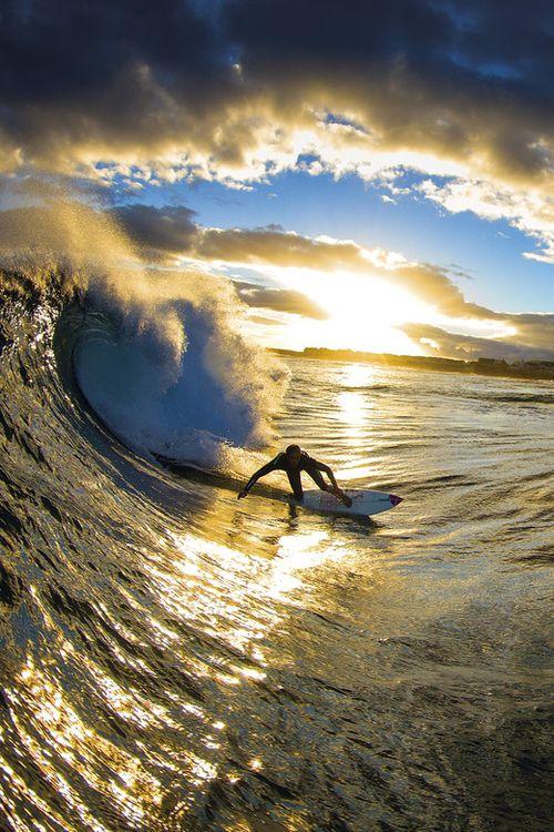 朝日とサーフィンする女性