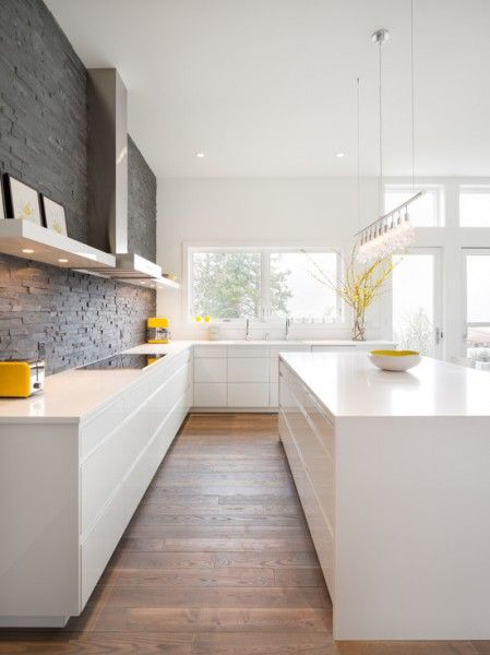 This kitchen looks like the perfect space, minimal white, split face tiles, wooden floor, even down to the mustard yellow coloured accessories. Similar split face tiles can be found at Mandarin Stone www.mandarinstone.com