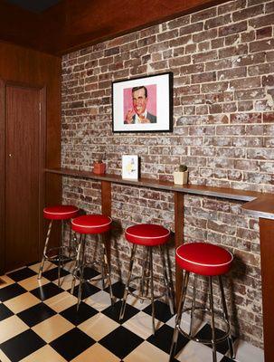 This would make a cool bar. Brick wall, red bar stools, checker floor. I love it.