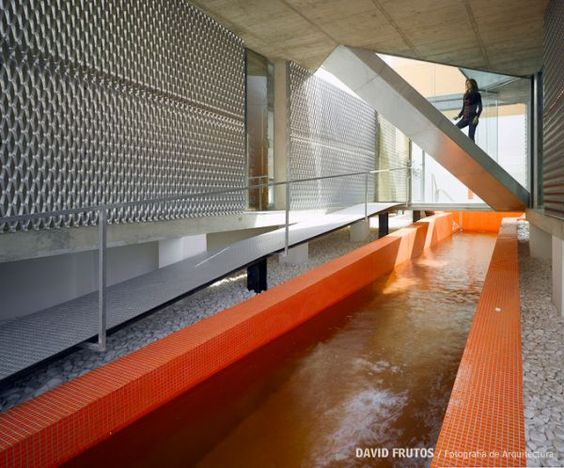 Orange swimming pool house - glassed in staircases / bridge connect two wings together over pool...