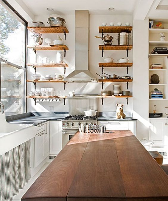 Use your kitchenware to your advantage by making it double as decor with these high wood shelves.
