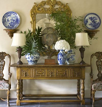 Gorgeous console, chairs, mirror, brackets with large plates plus blue and white pieces on the console. Well placed greenery. A little crowded but beautiful.