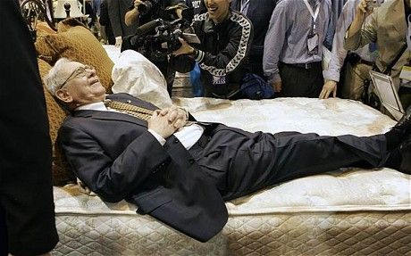 Billionaire investor Warren Buffett strikes a pose on a mattress during the annual Berkshire Hathaway shareholders meeting, in Omaha, Neb., Saturday, May 5, 2007.