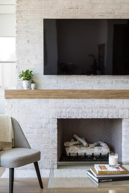 A Flat Panel Television Is Fixed To A White Brick Painted Fireplace Over A Rustic Wood White Brick Fireplace White Wash Brick Fireplace Painted Brick Fireplace