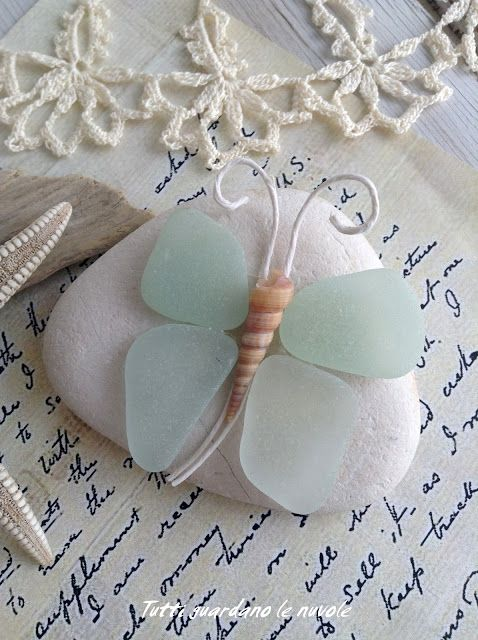 What a sweet butterfly paperweight or little piece of nautical decor made from sea glass, a weathered beach stone, and a shell.: