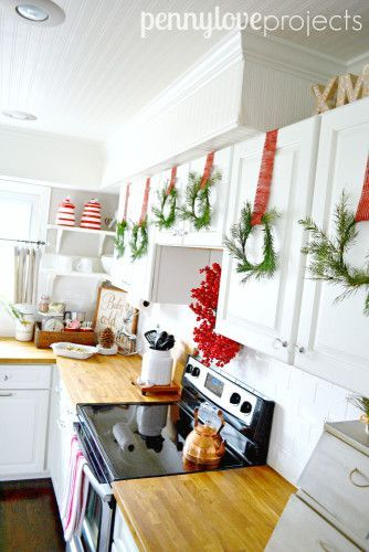 Decorate farmhouse style for Christmas. White kitchen hang wreaths from cabinets
