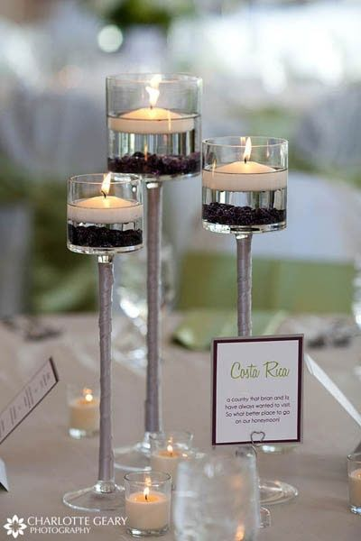 Floating candle centerpiece with 3 small flower pieces in greens and whites around it on the table.. black ribbon up the stem. Maybe use wine glasses for the vases?