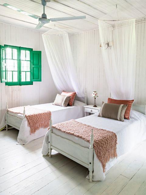 Dormitorio rústico con dos camas en blanco, verde agua y tonos tierra en una casa de campo de Chascomús. Foto: Javier Csecs