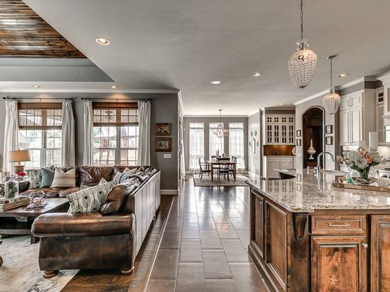 Grey walls, wood floors, white trim and brown leather sectional and accents