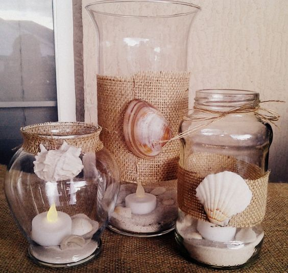 Burlap accented glass jars with seashells and beach sand for beach decorations.