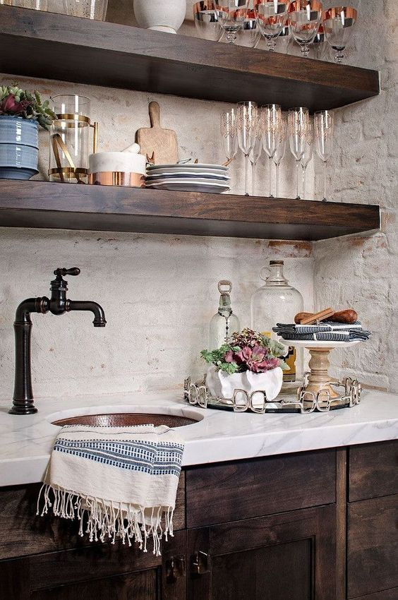 The rustic wood of the cabinets here really contrast with the marble and that is a really stylish look. The dark colors and the old-style faucet really help enhance that idea too.