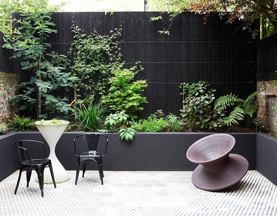 In the graphic-looking garden, a concrete raised bed and batten walls are painted black as a backdrop to the glossy green plants. The geometric concrete floor tiles were swapped with a friend. Try Mosaic del Sur for similar. The sculptural Spun chair is by Thomas Heatherwick for Magis, and a pair of black Tolix chairs from Made sit beside a concrete planter from Habitat, now discontinued.