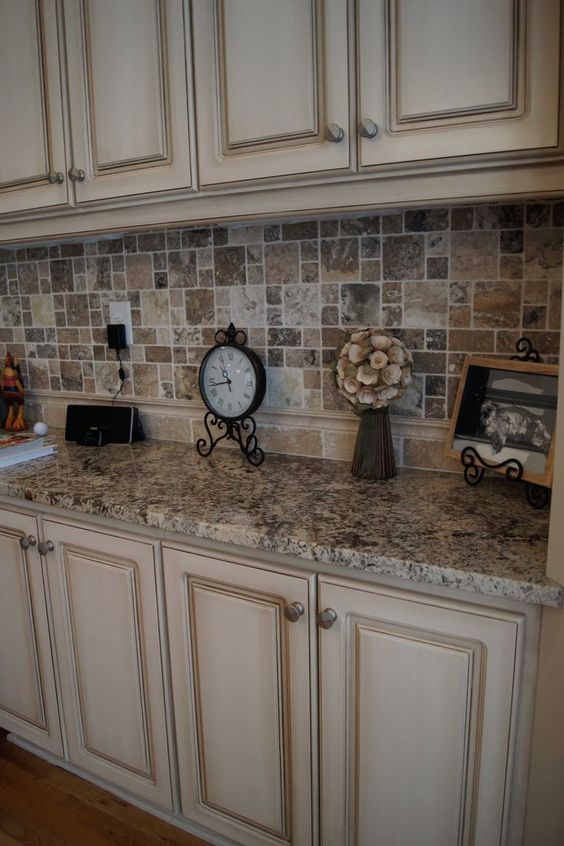 Cabinets refinished to a custom off white finish with heavy glaze and oh that backsplash!: