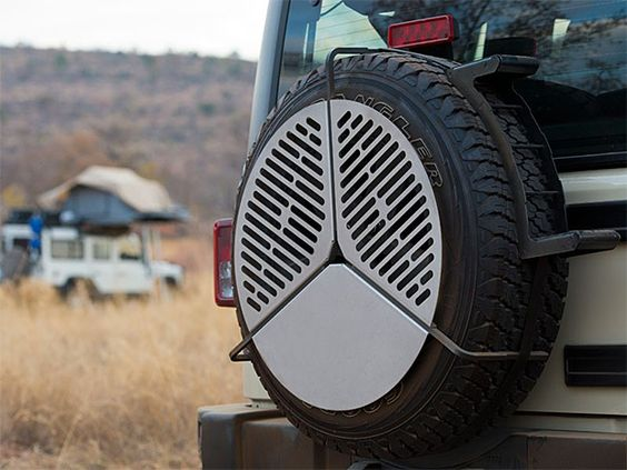 """Spare Tire Mount BBQ Grate Yes, your Jeep or FJ can crawl over tree stumps and climb effortlessly up mountainsides but fitting all your getaway gear inside isn't quite as easy. For you guys, this spare tire mounted stainless steel BBQ grate will give you a great place to grill without taking up precious cargo space inside your little four-by. Fits tires 29""""-37""""."""
