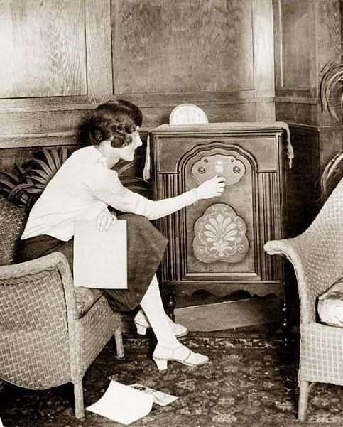 You are viewing an important image of Young woman tuning a radio. It was taken in between 1920 and 1932 Young woman tuning a radio