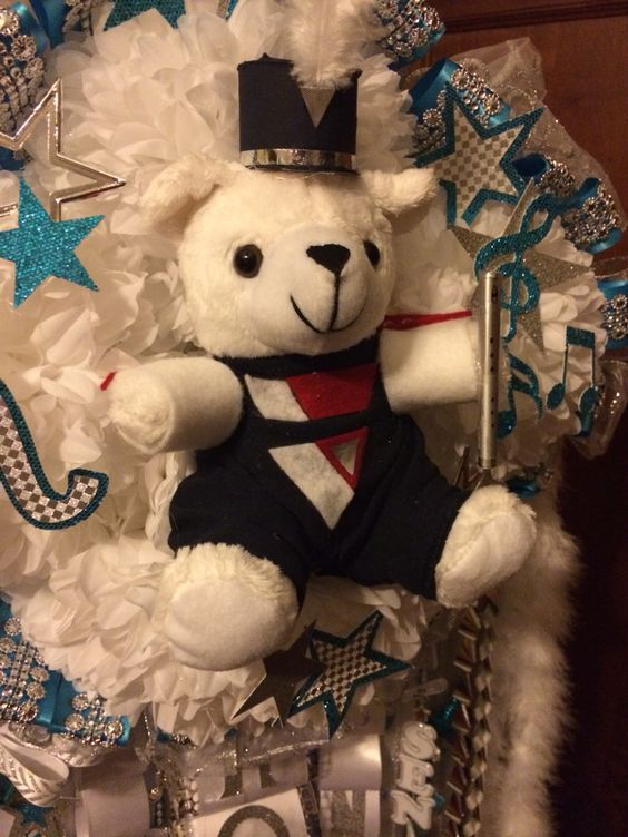Bear in band uniform made from scraps of fabric, glue, and pins. Hat is toilet paper roll and cardboard.