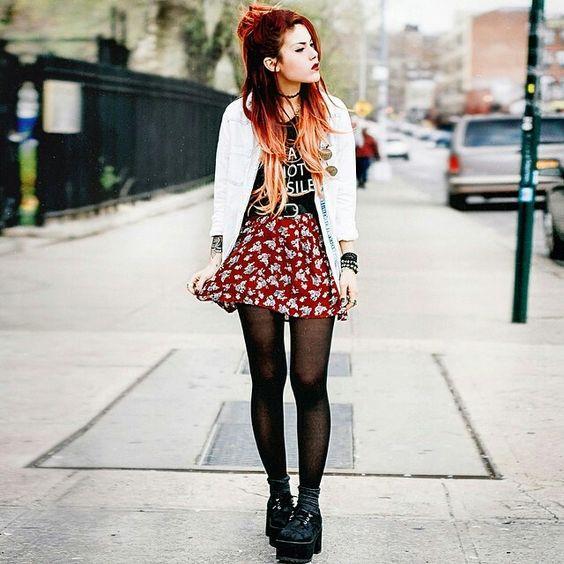 Llevo la falda de color rojo y las medias negros. Llevo el suéter blanco y la camiseta. Llevo las botas de la piel.:
