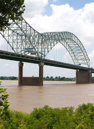"The Memphis - Arkansas bridge or the ""M"" bridge over the muddy Mississippi River connects Memphis to Arkansas."