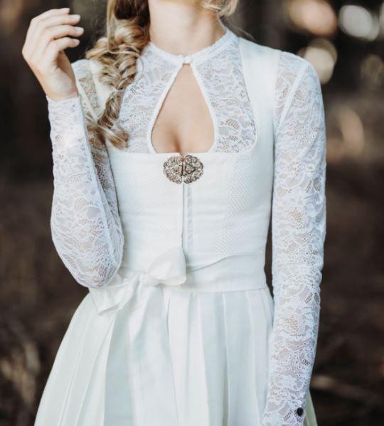 Das Hochzeitsdirndl Desire von AlpenHerz wird durch eine 80cm Rocklänge und einer schlichten Seidenschürze zu einem ganz besonderem Dirndl. Die Brosche verdeckt den Reißverschluss und passt perfekt zu dem eleganten Dirndl