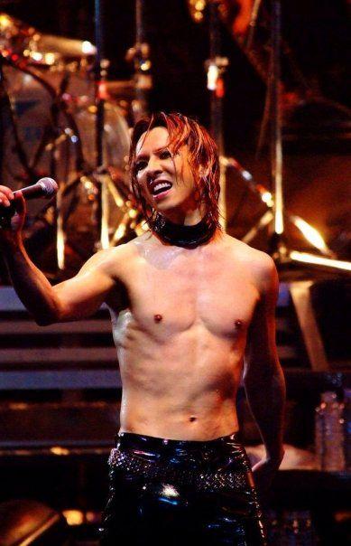 上半身裸でマイクを握って笑っているXJAPAN・YOSHIKIの画像
