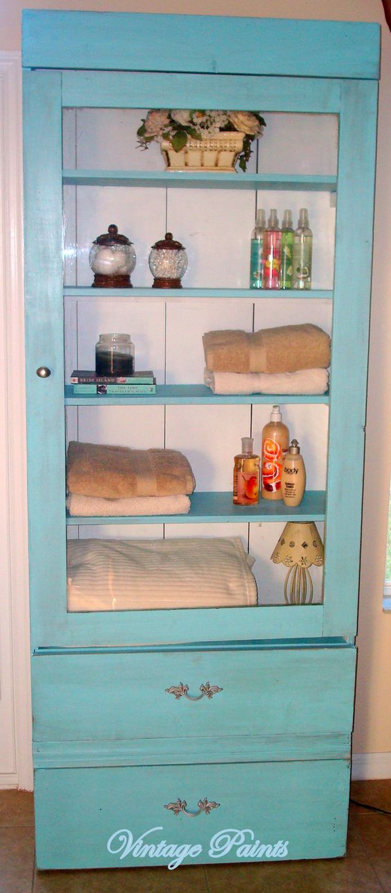 Ugly old gun cabinet converted into a great bathroom storage cabinet.  Painted Seagreen with Extra White on the back planks. Awesome Idea!
