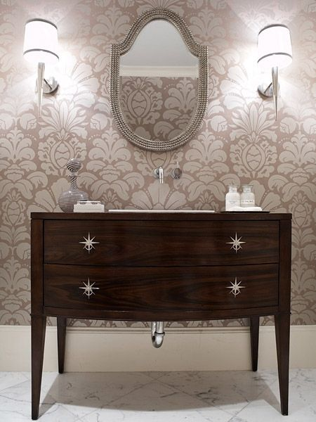 retrofitted the bureau into a one-of-a-kind sink vanity and custom-designed the polished-nickel starburst drawer-pulls. Other touches include Carrera marble floor tiles; modern, wall-mounted tap fixtures; elegant, Barbara Barry-designed torch sconces; an