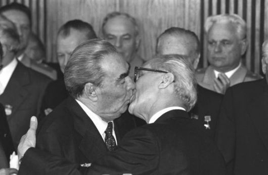 """10.7.1979 - East Berlin, DDR: The iconic photograph capturing the famed embrace was snapped by Regis Bossu. Brezhnev was visiting East Germany to celebrate the 30th anniversary of its founding as a Communist nation.  According to former Polish Communist leader Wojciech Jaruzelski, Honecker kissed many politicians in a """"disgusting way."""""""
