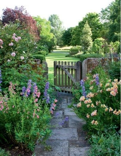 Do you know where this lovely #English #cottage style #garden is? I can't trace the place (or even the original photo source), but I'd love to have this lovely garden on the other side of my front or back door. Sadly no such luck. Blue delphiniums & pink climbing roses for sure. The other pink flowers might be penstemons on the left & alstromerias on the right? Love the rustic wooden gate & brick wall as well.
