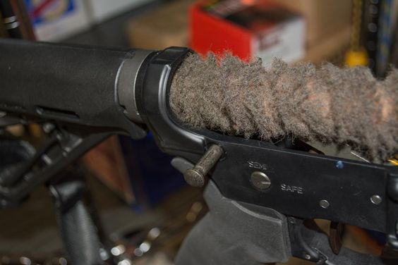 Using a shot gun bore mop to clean dirt and dust from buffer tube on your AR-15.