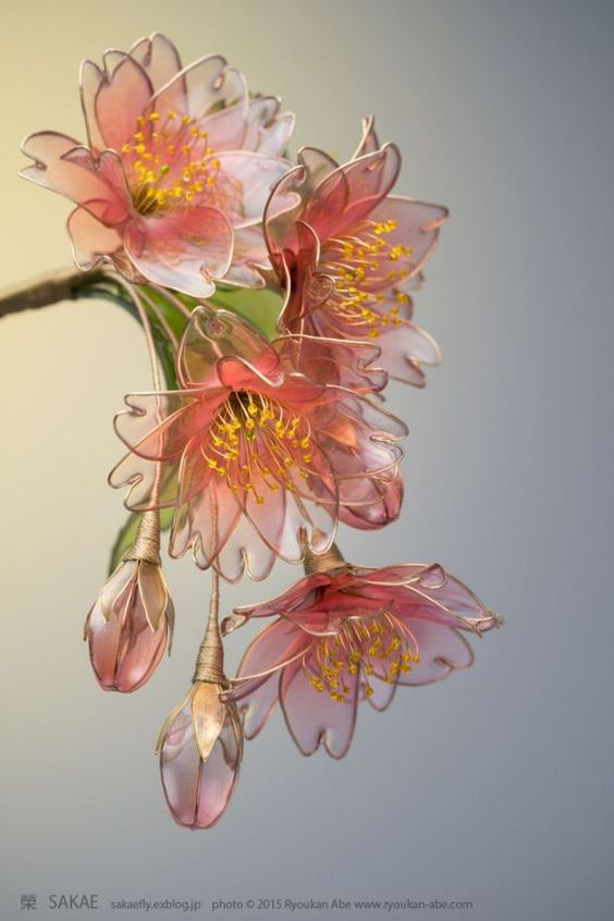 "These beautiful flowers may look like they are made of glass, but they are actually made from wire and liquid synthetic resin. Japanese Kanzashi (hair ornament) artist Sakae is the Maker behind this craft which she calls ""dip flower."" It involves bending a wire into a desired shape and then dipping it in a liquid plastic.:"