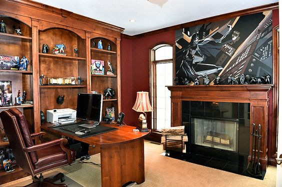Batman mural over fireplace in office with built-in bookcases