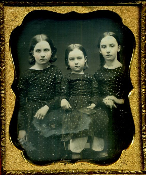 Three sisters in matching dresses.: