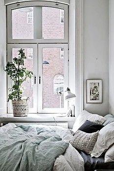 9 Astuces déco pour créer une ambiance cosy, cocooning dans votre chambre. Chambre mur blanc lit bleu défait coussins plante