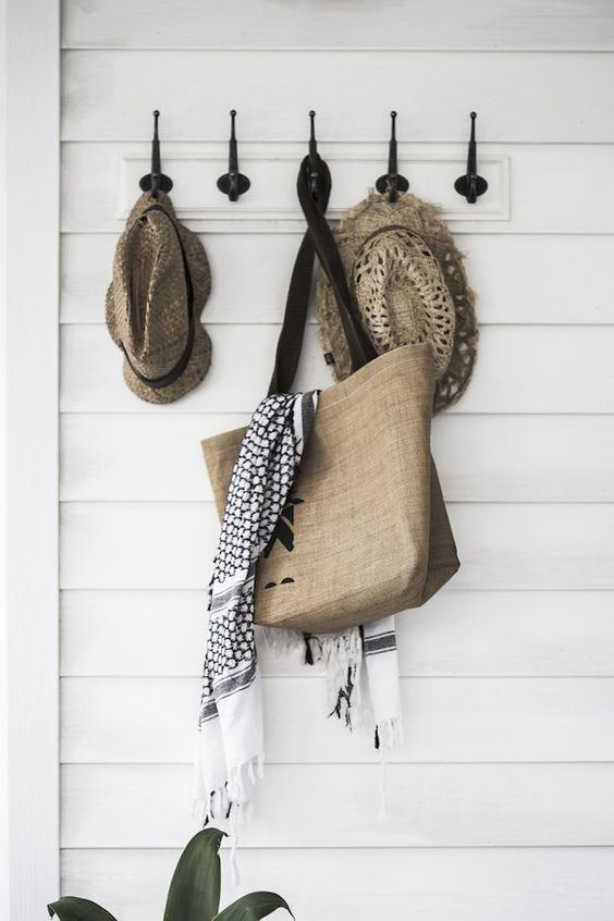 Hooks in the hallway of a pared-back Australian home in neutrals. Photographer: Maree Homer.: