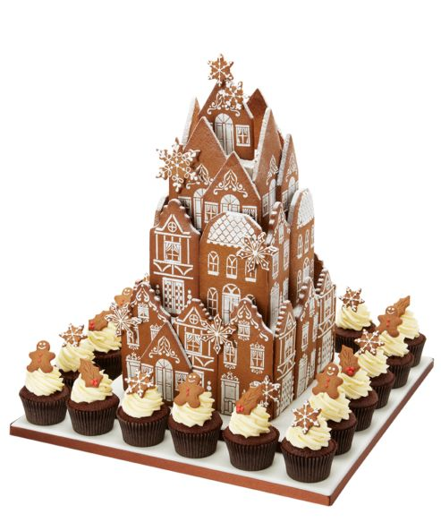 """Gingerbread Village Party Centrepiece  Decorated with 40 snow-topped gingerbread townhouse cookies and falling gingerbread snowflakes. This festive party centrepiece sits on a 18"""" square, ribbon-edged iced base board. The edible hand-piped cookies surround dummy tiers measuring 8""""/ 6""""/4"""" wide. This decorative party centrepiece is designed to delight and measures 20"""" tall. The Gingerbread Cookie Village is surrounded by 20 delicious Gingerbread Cupcakes"""
