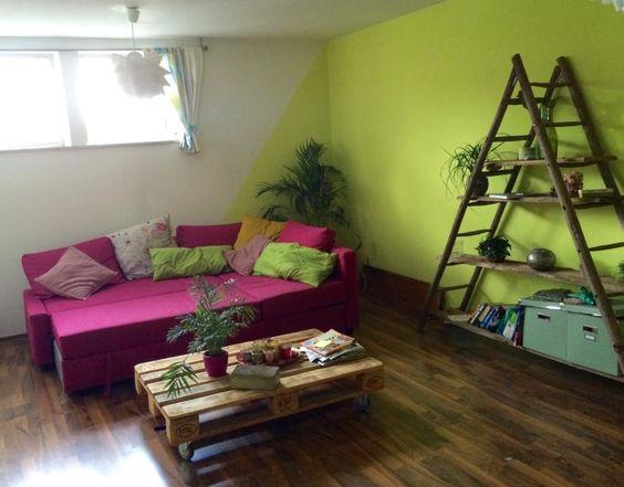 Farbenfrohes Wohnzimmer mit grüner Wand und pinkem Sofa sowie kreativem Couchtisch aus Europaletten.  WG-Zimmer in Mainz.  #Mainz #WGZimmer #Wohnung #livingroom