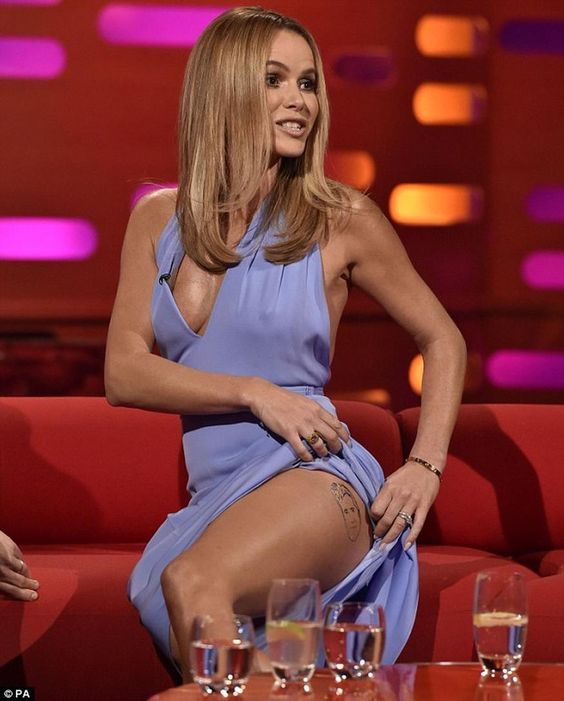 Amanda Holden reveals tattoo of Simon Cowell\'s FACE on her thigh... as she flashes the flesh in revealing lilac gown.  Amanda Holden showed off a startling new tattoo while filming an appearance on Graham Norton\'s chat show on Thursday, to be aired on BBC One on Friday.  The Britain\'s Got Talent judge pulled up her flowing lilac dress to reveal an inking of her boss Simon Cowell on her left thigh.