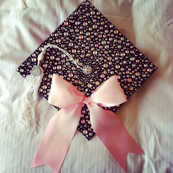 Pink Bow Graduation Cap. Congratulation to the graduate success with this elegant graduation cap with all its sparkling beadings as well as smooth pink ribbon bow to add up more beauty to this art piece. http://hative.com/graduation-cap-ideas/: