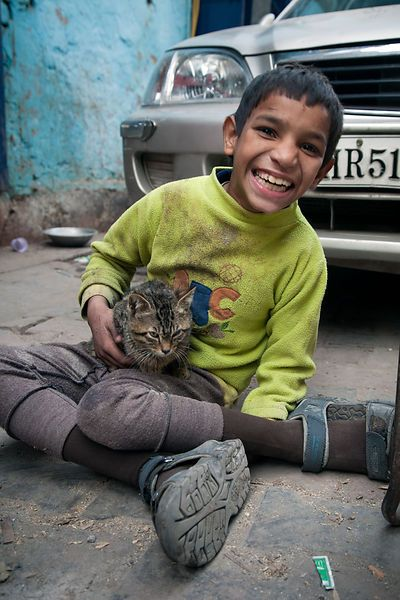A disabled boy and his cat in Delhi, India